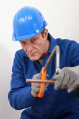 A tradesman using a saw to cut a copper tube — Stock Photo
