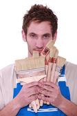 Decorator holding selection of paint brushes — Stock Photo