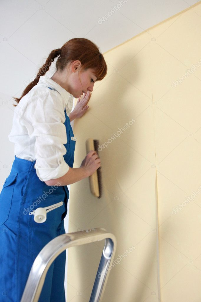 Woman smoothing wallpaper — Stock Photo #9670768