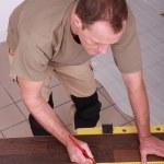 Man measuring slat parquet — Stock Photo #9680685