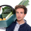 Young farmer with a vegetables basket - Stock Photo