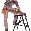 Handyman sawing a plank of wood - Stock Photo