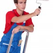 Painter with roller brush standing on ladder — Stock Photo