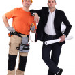 Engineer and construction worker standing side by side - Stok fotoğraf