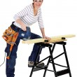 Woman sawing wood with electrical saw — Stock Photo