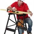 Stock Photo: Carpenter taking measures.