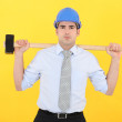 Architect holding sledge-hammer across shoulders - Stock Photo