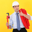 Businessman holding wrench and pipe — Stock Photo