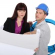 Construction worker and an engineer looking at a drawing — Stock Photo #9682919