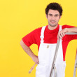 Painter leaning against ladder - Stock Photo