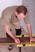 Man measuring slat parquet — Stock Photo