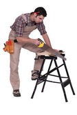 Handyman sawing a plank of wood — Stock Photo