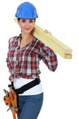 Attractive woman carrying planks of wood — Stock Photo