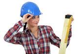 Female carpenter measuring wood — Stock Photo