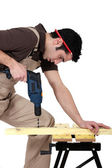 Carpenter drilling a piece of wood — Stock Photo
