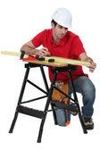 A carpenter taking measures. — Stock Photo