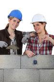 Zwei handwerkerinnen bau einer mauer — Stockfoto