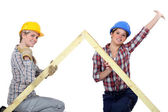 Peppy tradeswomen holding up a wooden frame — Stock Photo