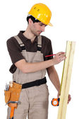 Tradesman measuring a plank of wood — Stock Photo