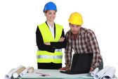 Businesswoman and craftsman examining a project — Stock Photo