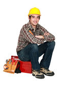 Portrait of young craftsman sitting on toolcase — Stock Photo