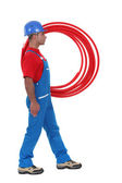Plumber carrying pipes. — Stock Photo