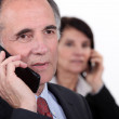 Two businesspeople making phone calls — Stock Photo