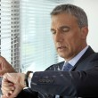Senior businessman checking the time — Stock Photo
