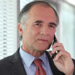 Senior businessman negotiating over the phone - Stock Photo