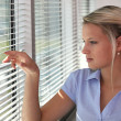 Blond office worker peering through window blinds — Stock Photo #9704838