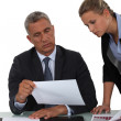 Mature businessman and young blonde assistant — Stock Photo