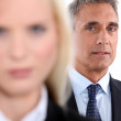 Male executive with female colleague out of focus in the foreground — Stock Photo #9705665