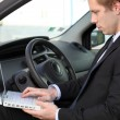 Businessman using laptop in his car — Stockfoto