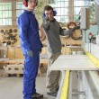 Carpenter and apprentice using industrial saw — Foto Stock