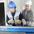 Two men operating machine than cuts sheet metal - Stock Photo