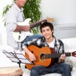Stock Photo: Father teaching son how to play the guitar