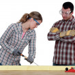 Female carpenter at work with male workmate watching her — Stock Photo #9706973