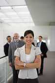 Smiling businesswoman standing cross-armed in workplace — Stock Photo