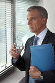 Businessman looking through his office window — Stock Photo