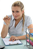 Businesswoman holding a pen and looking at her agenda — Stock Photo
