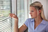 Blond office worker peering through window blinds — Stock Photo