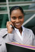 Businesswoman stood with cellphone and folders — Stock Photo