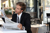 Executive reading a newspaper on the terrace — Stock Photo