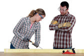 Female carpenter at work with male workmate watching her — Stock Photo