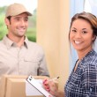 Delivery man and young woman — Stockfoto