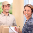 Delivery man and young woman — Stock Photo