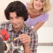 Stock Photo: Couple repairing their television