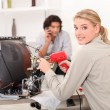 Stock Photo: Womrepairing television with soldering iron