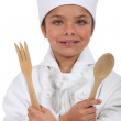 Teenage girl dressed in cook costume holding wooden spoon and fork — Stock Photo #9723785