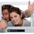 Stock Photo: Couple popping out TV.